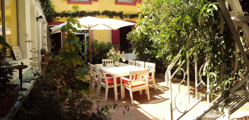 Le patio arboré et la table de la salle à manger d'été